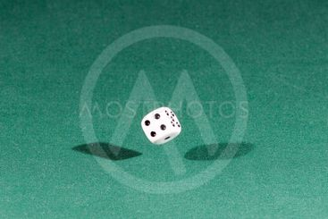 One white dice falling on a green table
