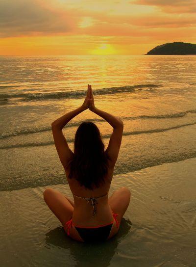 Young woman in bikini sitting on a beach at sunset,...