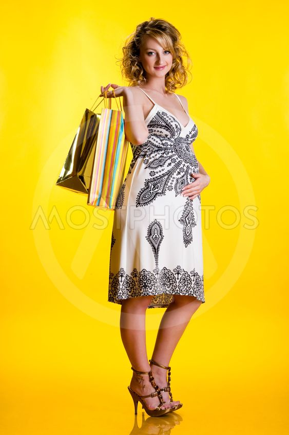 Lovely pregnant woman holding shopping bags