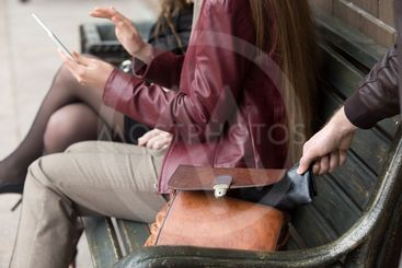 Thief stealing wallet from woman sitting on a bench