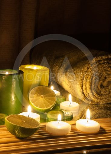 Spa and wellness setting green and yellow candles lit,...
