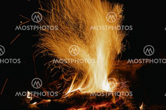 Sparks from fire in dark. Tourist night bonfire.