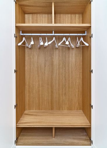 White wardrobe with wooden drawers and shelves. Wooden...
