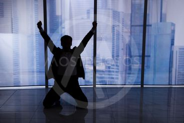 Businessman Sitting Arms Outstretched By Office Window