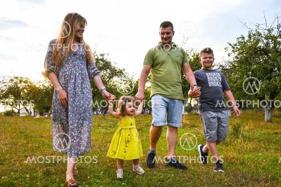 Happy family enjoying in park. Cute Portrait of Happy...