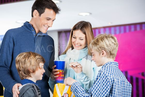 Family Enjoying Snacks At Cinema