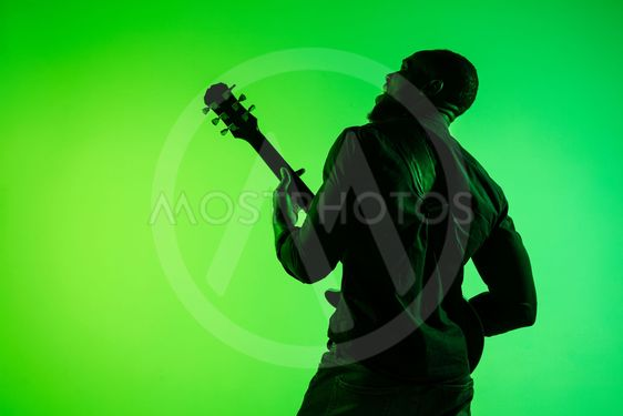 Young african-american jazz musician playing the guitar