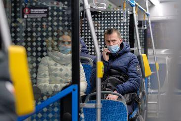 A young man in a face mask sits on a seat in a city bus...