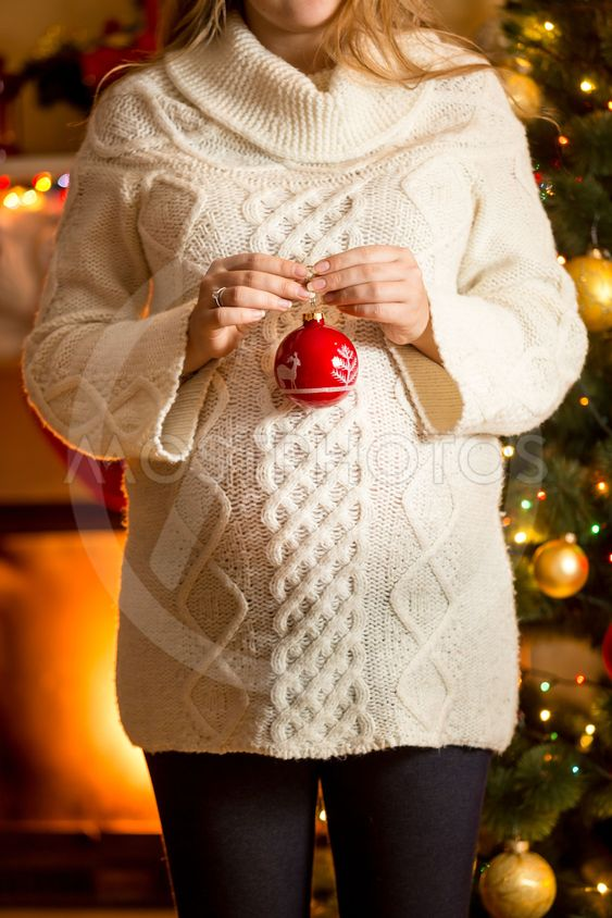 pregnant woman posing against fireplace with Christmas ball