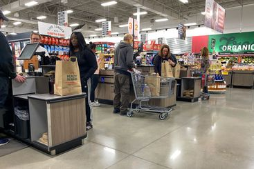 Grocery store employees scanning food items at the check...