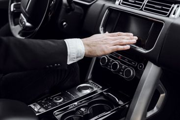 Male hand is switching radio in automobile