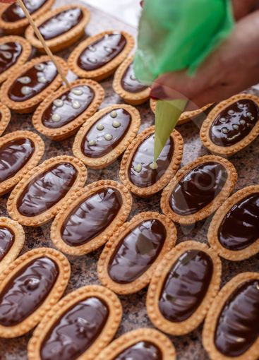 Woman hand decorating mini tarts