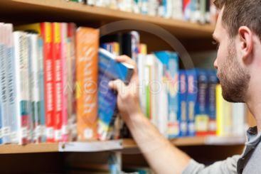 Handsome male student picking a book