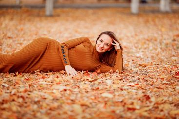 pregnant woman lies on leaves in autumn Park