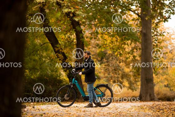 Young man with electric bicycle in te autumn park