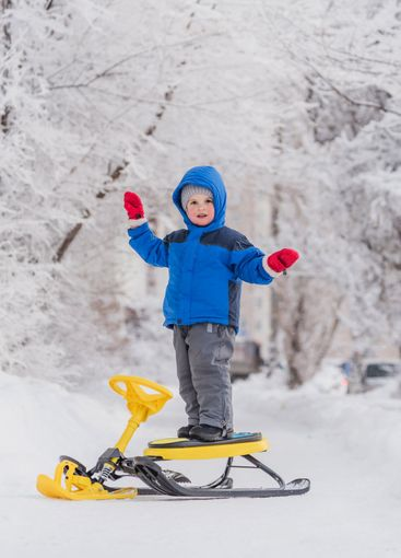 a small child stands on a snow scooter in winter