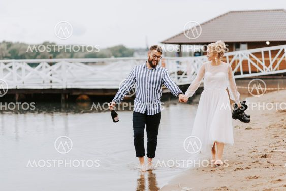 Young spouses go along the beach line barefoot and hold...