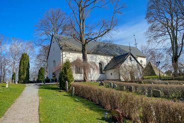 Järfälla kyrka med gravar gångväg och blå himmel.
