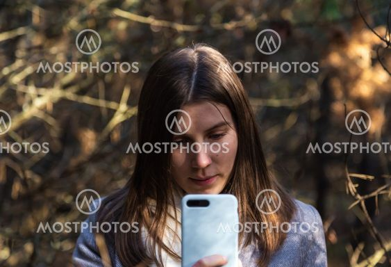Girl in a gray coat takes a selfie in the forest....