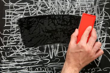 Cleaning a blackboard with a red chalk duster.