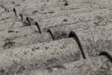 Old roofing tiles made of asbestos and cement. Dangerous...