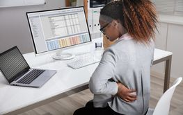 Businesswoman Suffering From Backache While Working In...