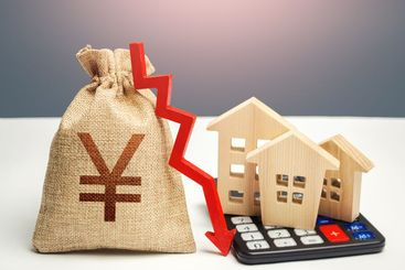 Yuan Yen money bag with down arrow and houses on...