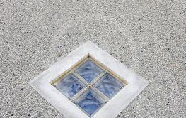 Grå stenvägg med små fönster.