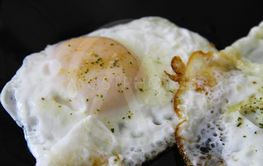 Roasted eggs on the black plate and dill over closeup