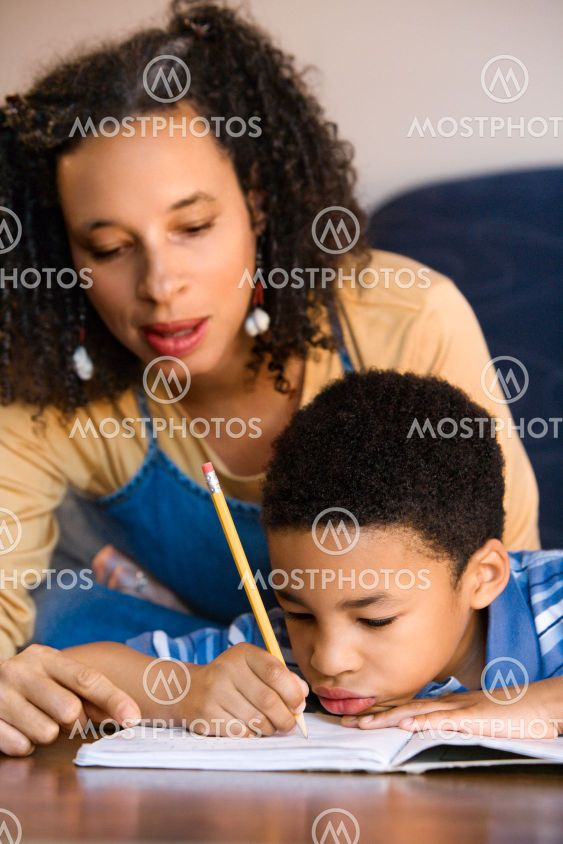 Mother helping son do homework.