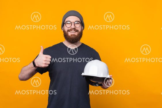 Photo of cheerful bearded man showing thumb up and...