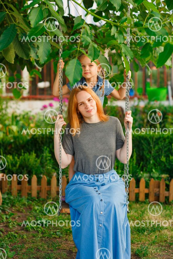 mom and daughter on swing in garden