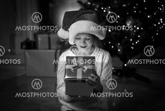 portrait of happy amazed girl looking inside of Christmas...
