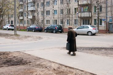 Aging. A lonely elderly hunched woman with a stick walks...