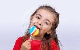 Little girl eating a lollipop.