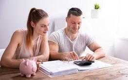 Couple Calculating Bills Using Calculator Near Piggy Bank