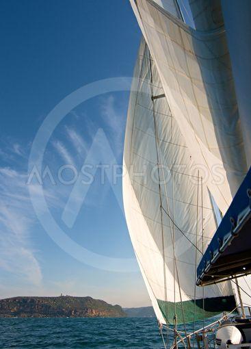 Sailboat at Sea Under Full Sail with Landfall in the...