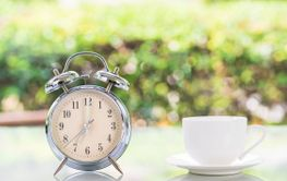 Silver alarm clock and white coffee cup