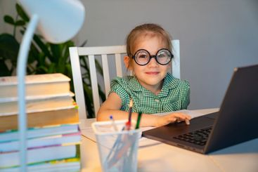 small girl in big glasses learning on laptop.