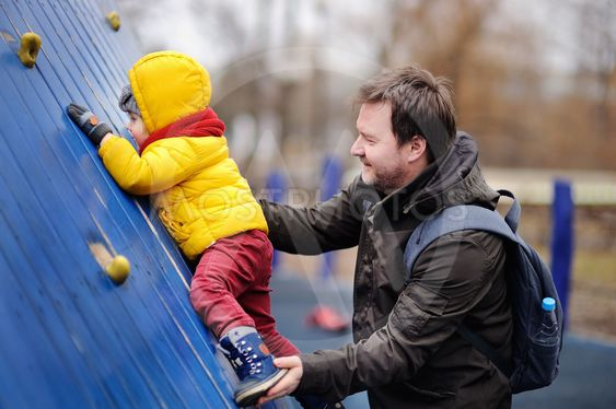 Happy little boy with his father having fun on outdoor...
