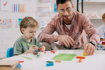 portrait of teacher and adorable preschooler with...