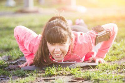 Young Woman Doing Push-Ups Exercises at Park.