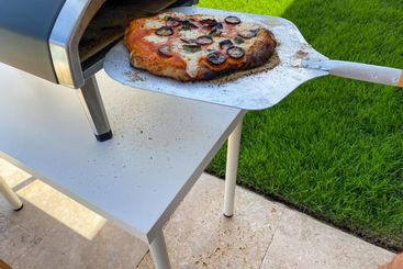 Homemade pizza being cooked on wood fired oven