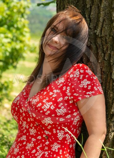 Happy friendly young woman leaning on a tree