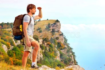 Man Traveler with backpack looking forward outdoor with...