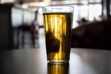 Närbild av guldfärgat glas med öl på en servering.