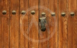 Ancient Wooden Door with Rivets and Door Knocker