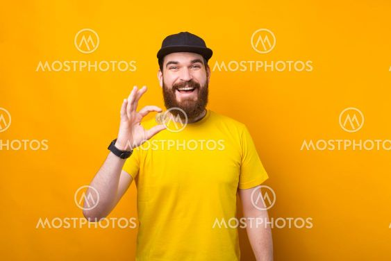 A young bearded man is holding excited a bitcoin looking...