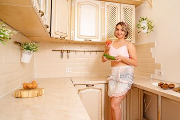 sexy blonde housewife with tomatoes and cucumbers at...