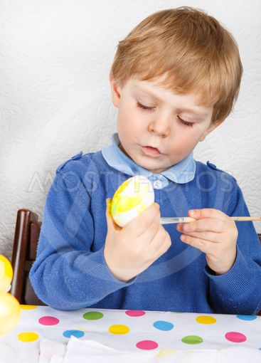 Little toddler boy painting colorful eggs for Easter hunt